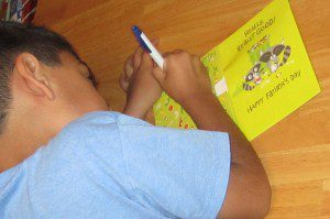 Kaindan writing in his dad's Father's Day card